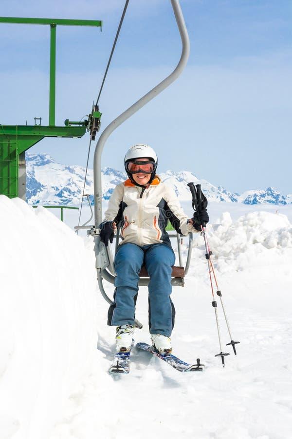 Счастливый женский лыжник ехать подъем стоковая фотография