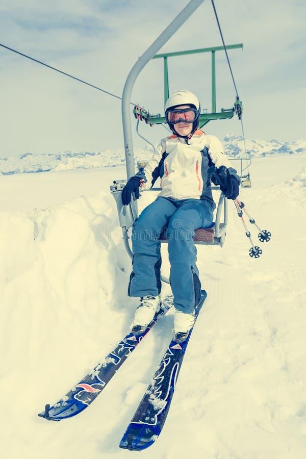 Счастливый женский лыжник ехать подъем стоковое фото rf