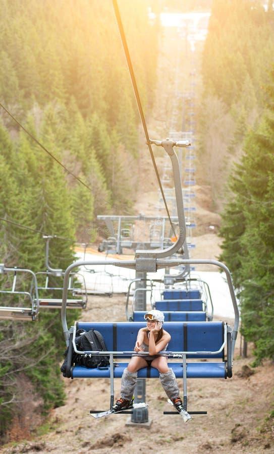 Счастливый женский лыжник сидит на подъеме лыжи и едет до верхней части горы и показывает большие пальцы руки вверх стоковые изображения rf