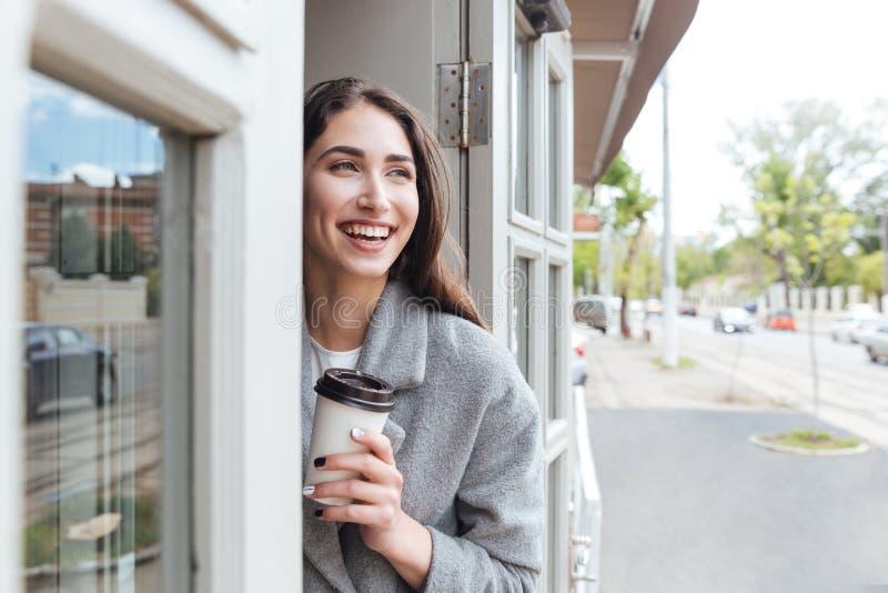 Счастливый жизнерадостный усмехаясь кофе взятия удерживания девушки отсутствующий стоковое изображение rf