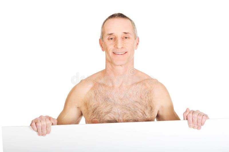 Счастливый зрелый без рубашки человек держа пустое знамя стоковая фотография
