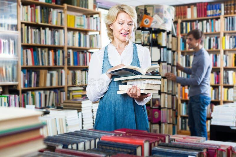 Счастливый зрелый женский клиент смотря открытую книгу стоковое фото rf