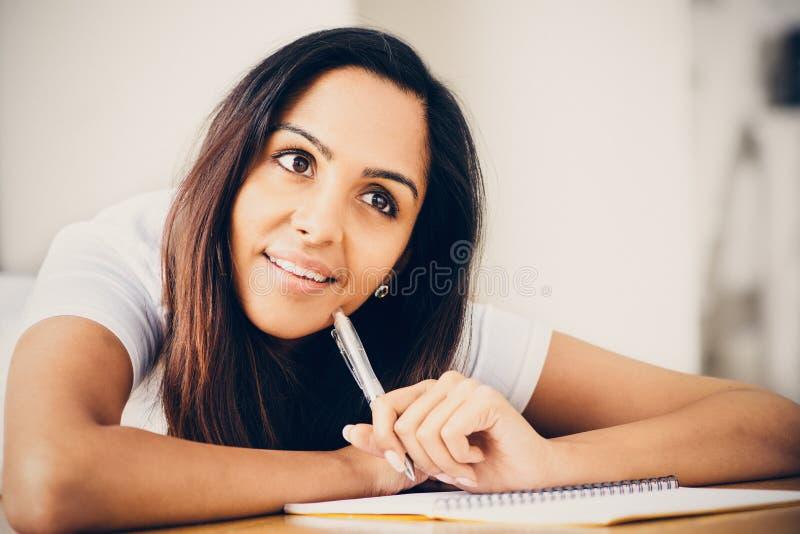 Счастливый индийский изучать сочинительства образования студента женщины стоковое фото rf