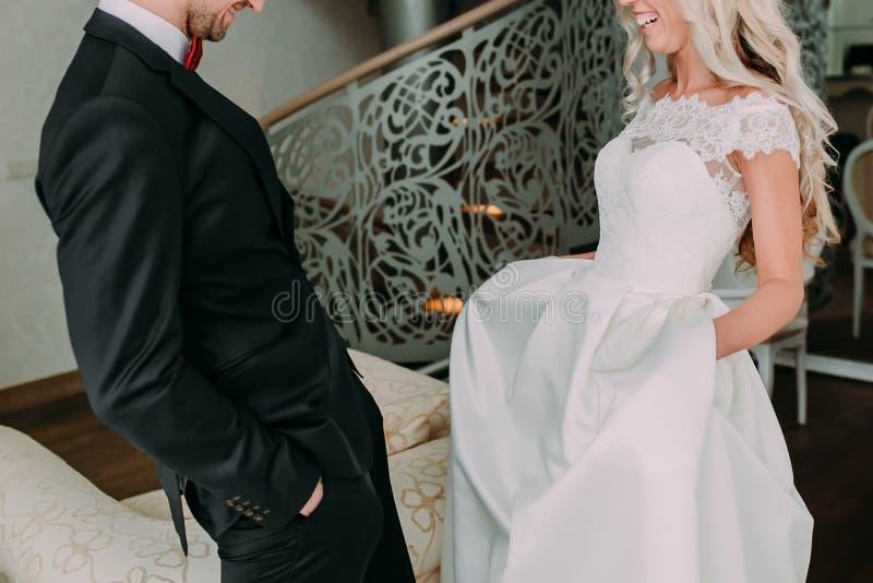 Счастливый и эмоциональный момент первого собрания groom и невесты на их день свадьбы лестницы портрета платья принципиальной схе стоковое фото rf