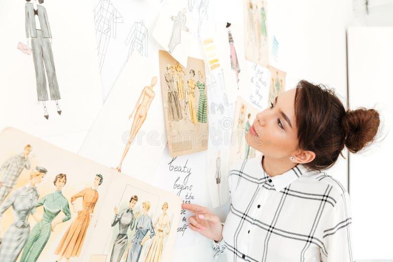 Счастливый иллюстратор моды дамы стоя около много иллюстраций стоковые фото