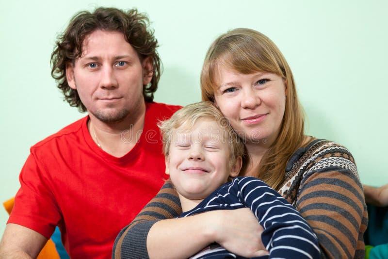 Счастливый кавказский портрет семьи обнимать с усмехаясь сыном стоковые фотографии rf