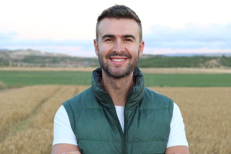 Счастливый красивый фермер показывать в поле готовом для сбора давать большой палец руки вверх стоковая фотография