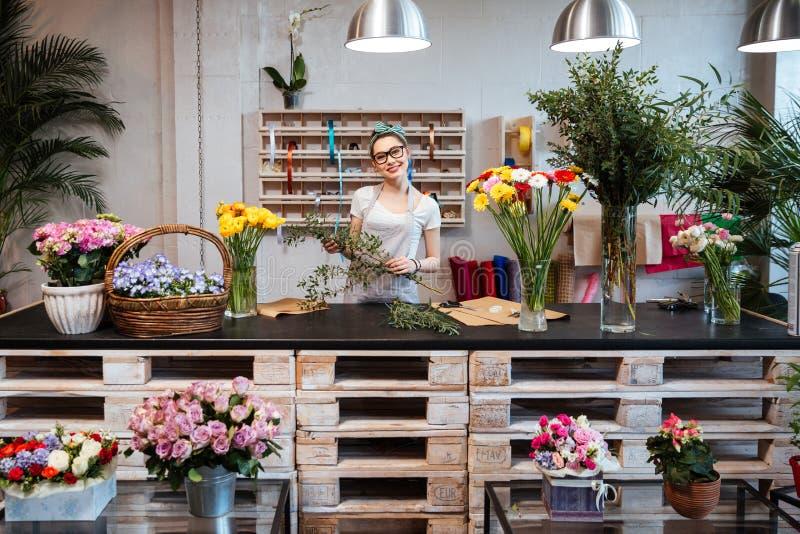 Счастливый красивый флорист молодой женщины стоя в цветочном магазине стоковая фотография rf