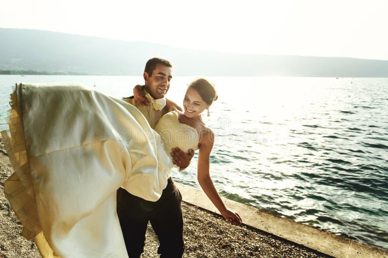 Счастливый красивый groom держа невесту в его оружиях на пляже на sunse стоковые фотографии rf