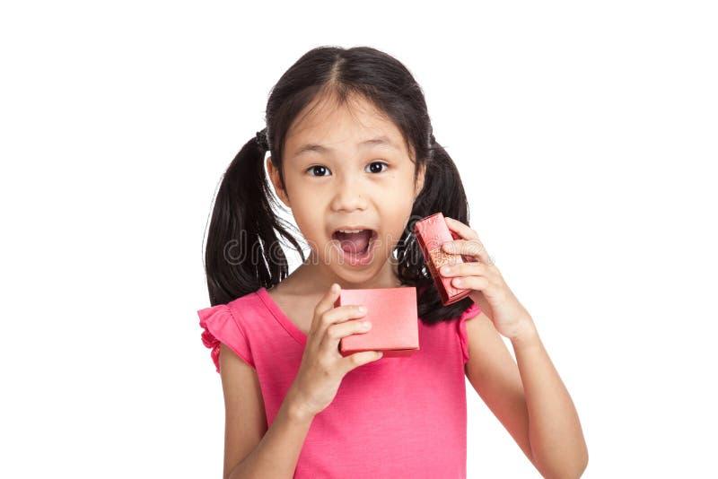 Счастливый маленький азиатский сюрприз девушки с красной подарочной коробкой стоковое изображение
