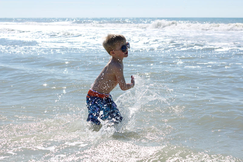 Счастливый маленький ребенок играя в океане стоковое фото