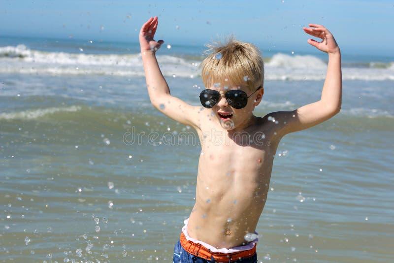 Счастливый маленький ребенок играя в океане стоковые изображения