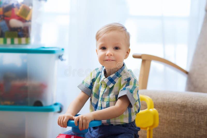 Счастливый маленький ребёнок управляя езд-на автомобиле дома стоковая фотография rf