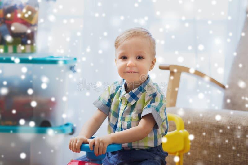 Счастливый маленький ребёнок управляя езд-на автомобиле дома стоковое фото rf