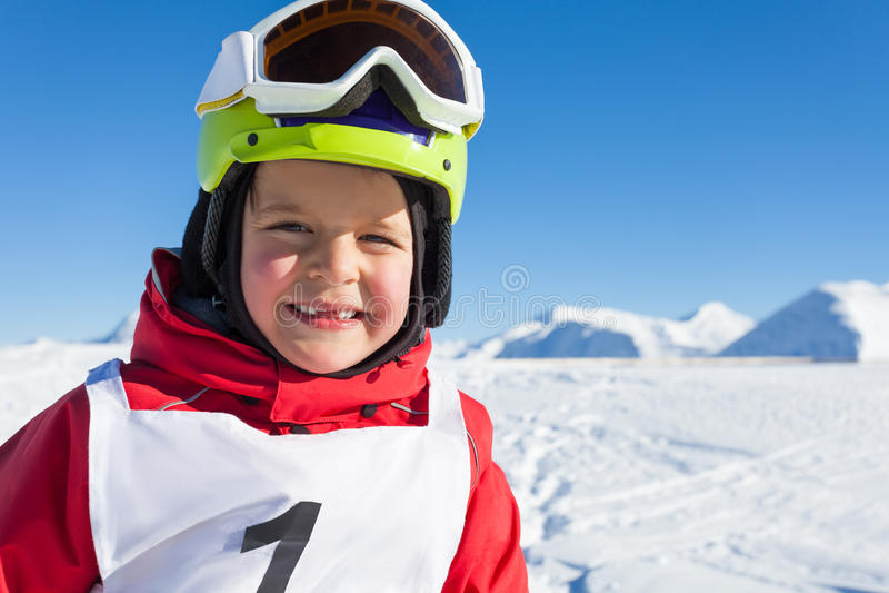 Счастливый маленький лыжник в шлеме и изумлённых взглядах безопасности стоковая фотография
