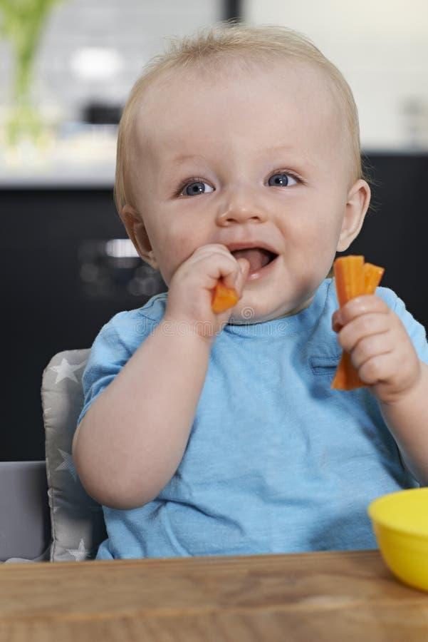 Счастливый малыш сидя на таблице есть свежие морковей стоковая фотография rf