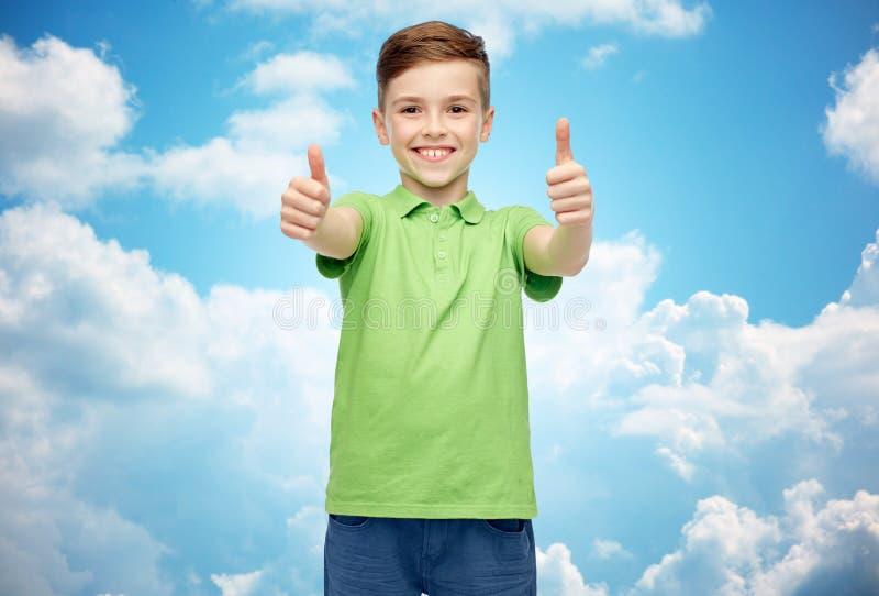 Счастливый мальчик в зеленой футболке поло показывая большие пальцы руки вверх стоковая фотография rf