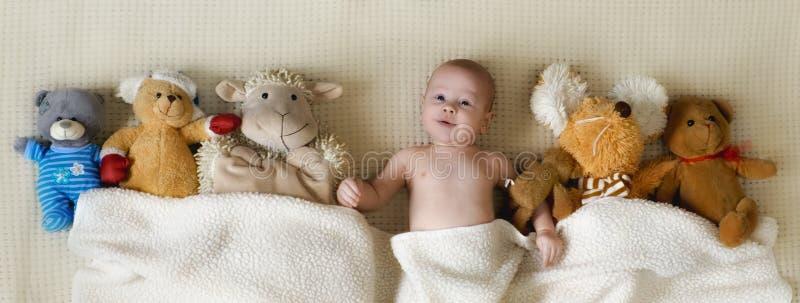 Счастливый мальчик лежа с много игрушек плюша под одеялом стоковые фотографии rf