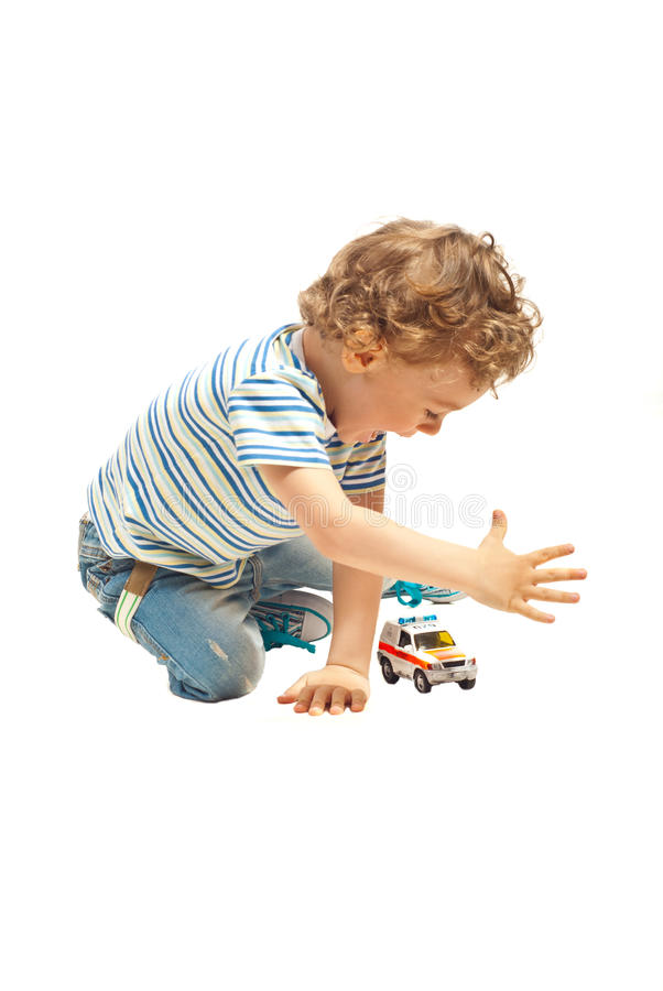 Счастливый мальчик играя с игрушкой автомобиля стоковое изображение