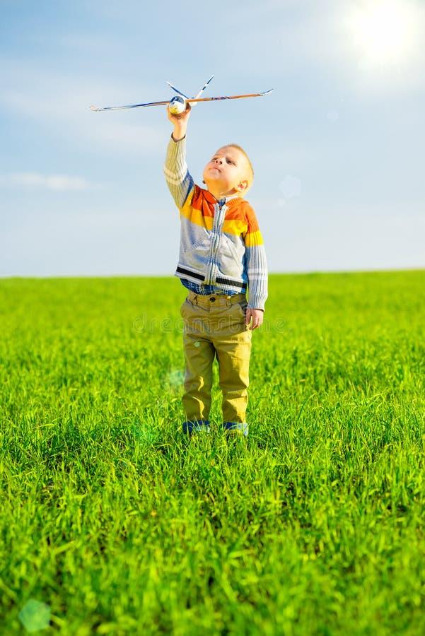 Счастливый мальчик играя с самолетом игрушки против голубого неба лета и зеленой предпосылки поля стоковое изображение rf