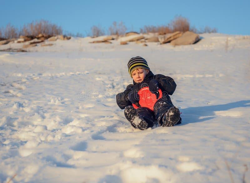 Счастливый мальчик имея потеху в снеге зимы стоковые фотографии rf