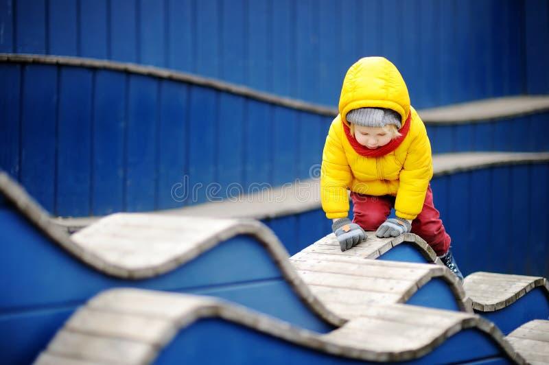 Счастливый мальчик имея потеху на внешней спортивной площадке стоковая фотография rf