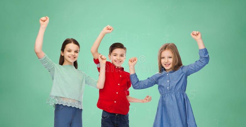 Счастливый мальчик и девушки празднуя победу стоковое фото