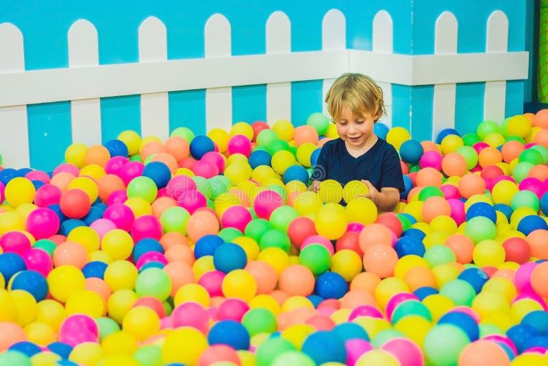 Счастливый мальчик маленького ребенка играя на взгляде красочной пластичной спортивной площадки шариков высоком Смешной ребенок и стоковые изображения rf