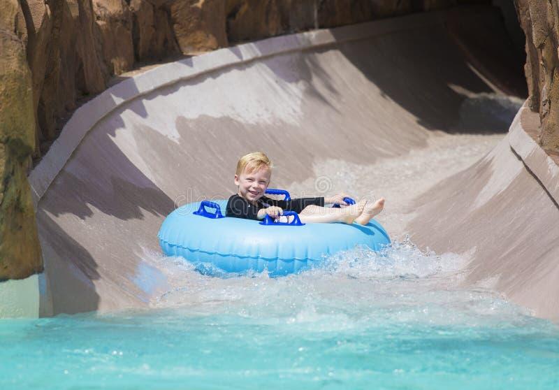 Счастливый мальчик наслаждаясь влажной ездой вниз с водных горок стоковое фото