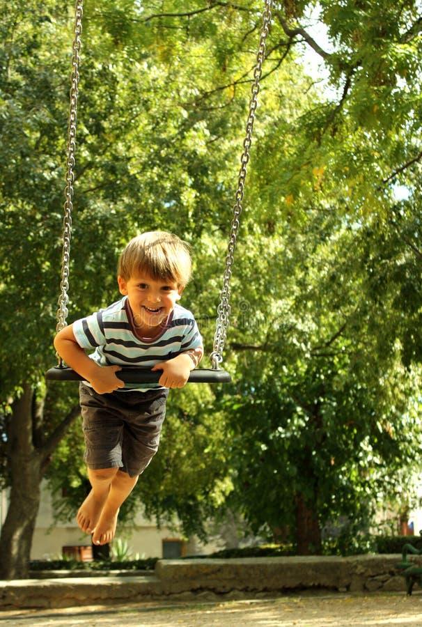 Счастливый мальчик на качании 5 стоковая фотография