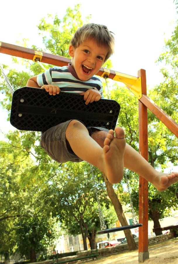 Счастливый мальчик на качании 1 стоковая фотография rf