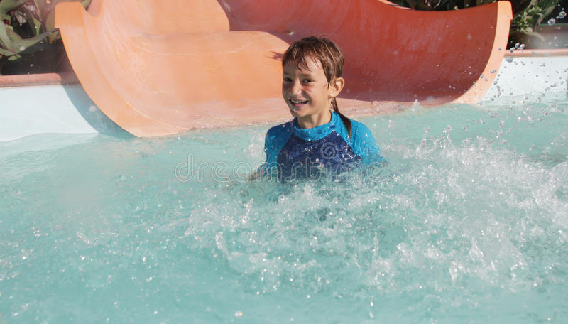 Счастливый мальчик ребенка имея потеху в аквапарк стоковое изображение
