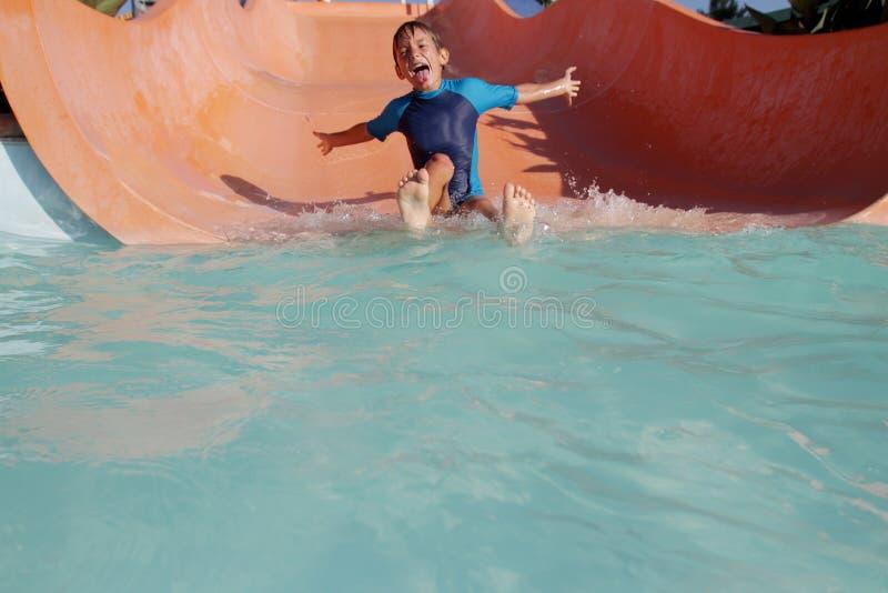 Счастливый мальчик ребенка имея потеху в парке воды стоковые фотографии rf