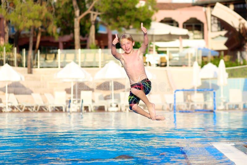 Счастливый мальчик скача в бассейн стоковые изображения rf