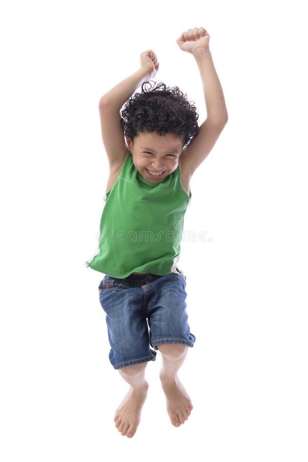 Счастливый мальчик скача с утехой стоковое изображение