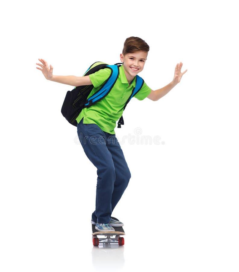 Счастливый мальчик студента с рюкзаком и скейтбордом стоковое изображение rf