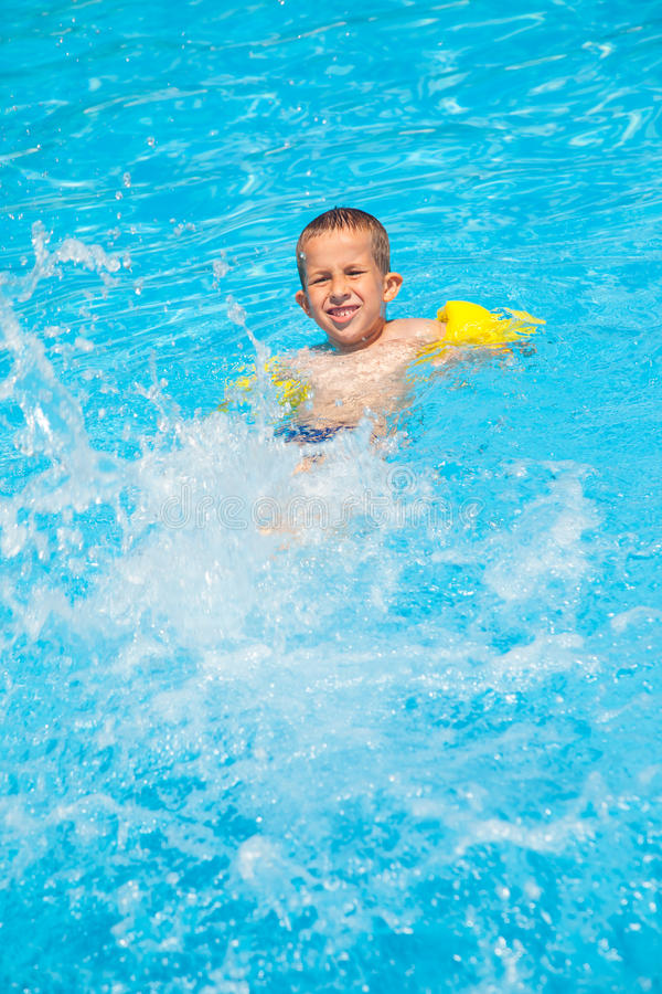Счастливый мальчик с кольцами воды имеет потеху стоковое фото