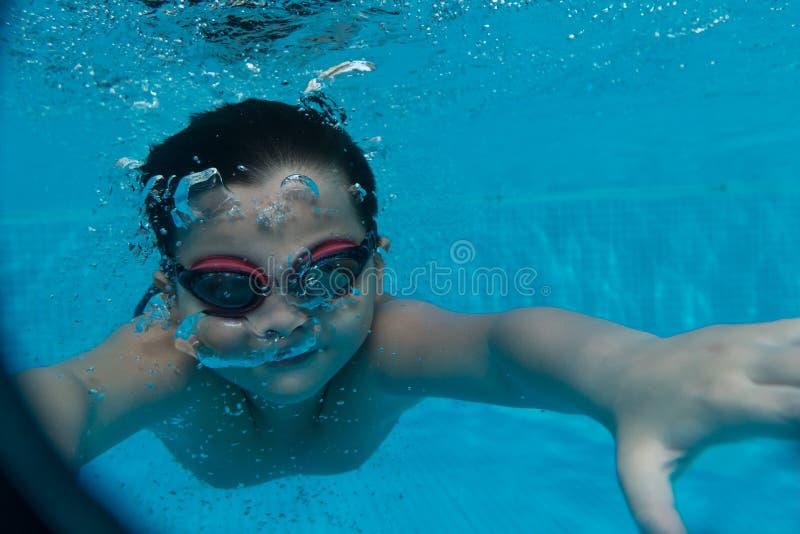 Счастливый молодой азиатский ребенк с изумлёнными взглядами заплыва подводными стоковое изображение
