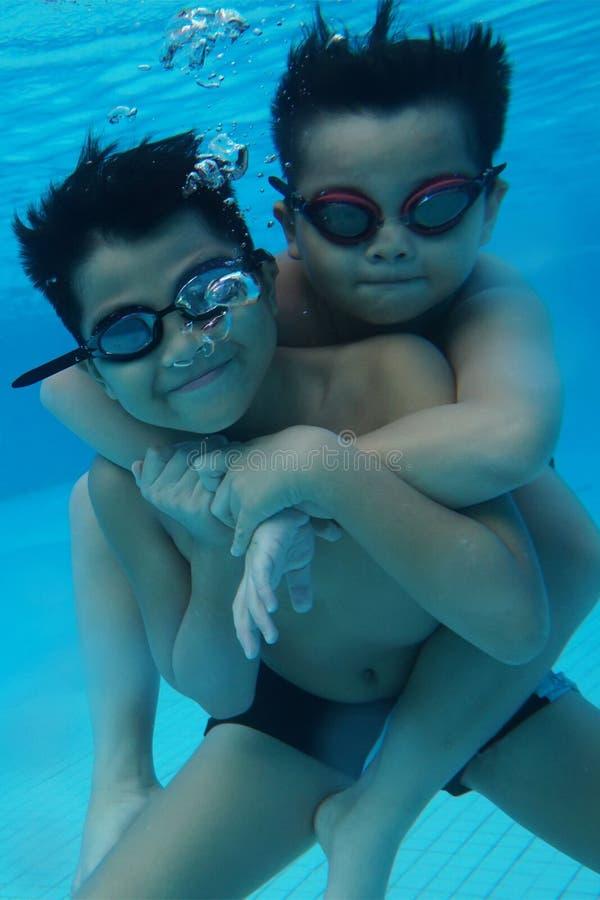 Счастливый молодой азиатский ребенк с изумлёнными взглядами заплыва подводными стоковые фотографии rf
