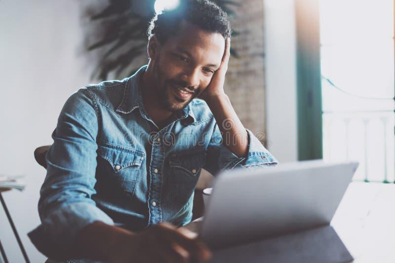 Счастливый молодой африканский человек делая видео- переговор звонка через цифровую таблетку с деловыми партнерами пока сидящ на  стоковые изображения