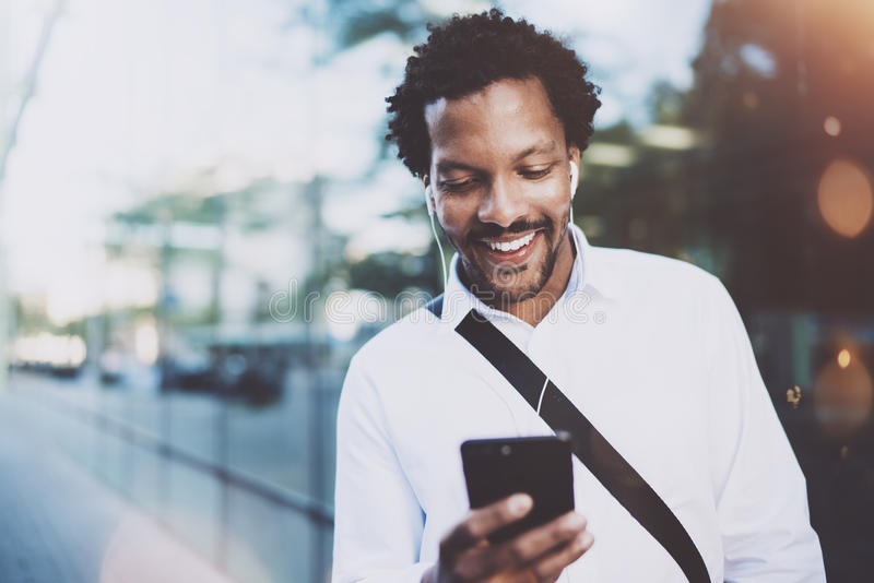 Счастливый молодой Афро-американский человек в наушниках идя на солнечный город и делая видео- переговор с друзьями на его стоковые фотографии rf