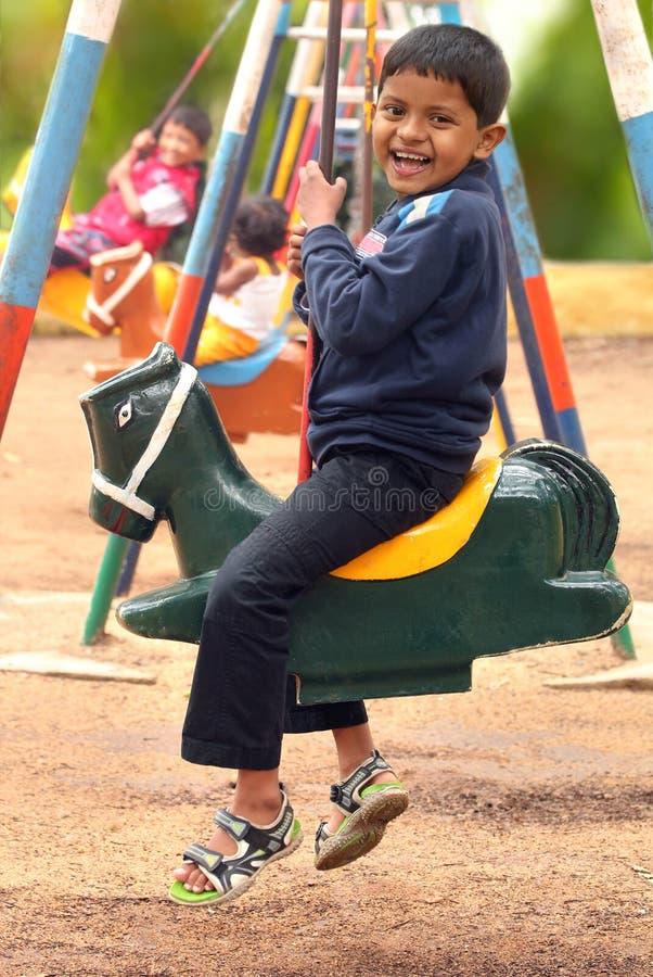 Счастливый молодой красивый мальчик (ребенк) играя на качании устанавливает в парк стоковые изображения