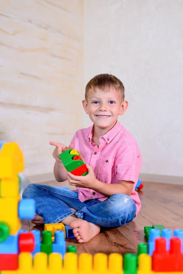 Счастливый молодой мальчик играя с его строительными блоками стоковые изображения rf