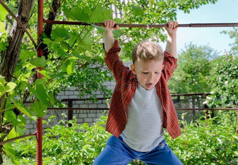 Счастливый молодой мальчик отбрасывая на металлическом стержне стоковое изображение rf