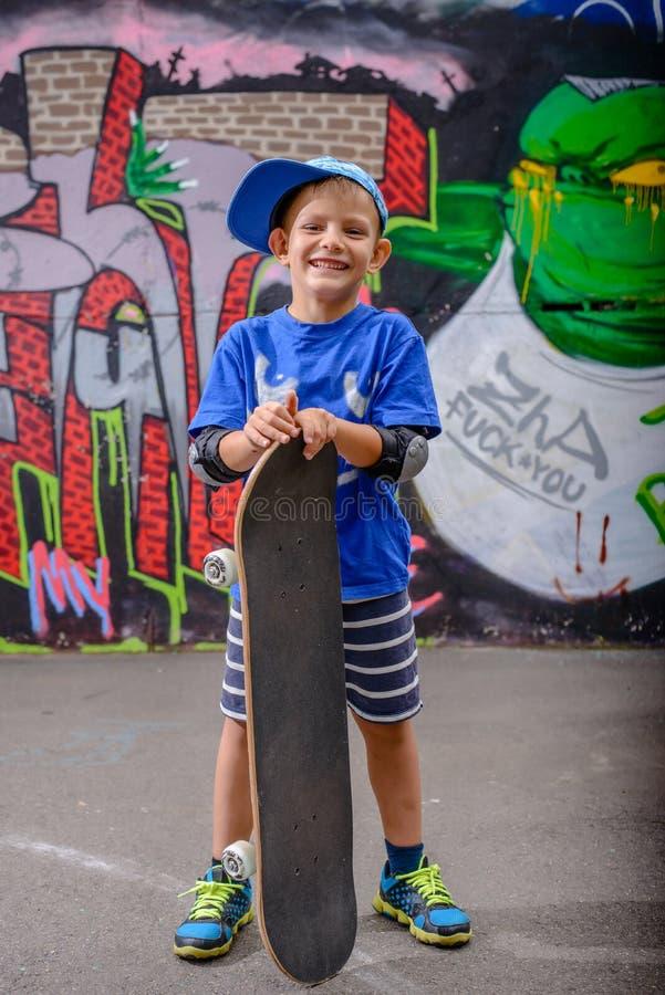 Счастливый молодой мальчик представляя с его скейтбордом стоковые фотографии rf