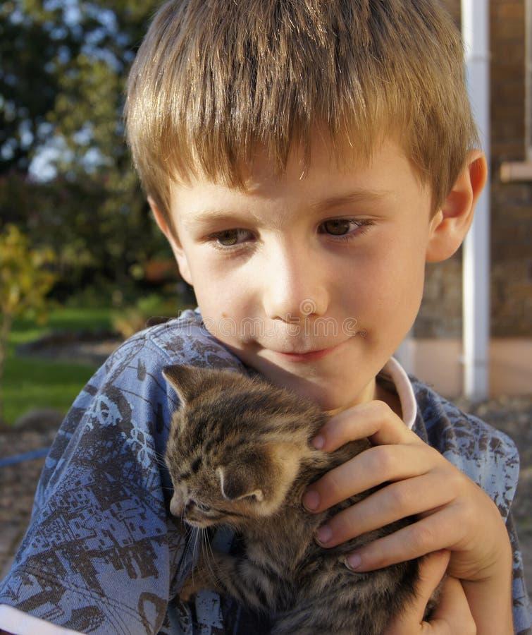 Счастливый молодой мальчик с молодым котенком любимчика стоковые изображения rf