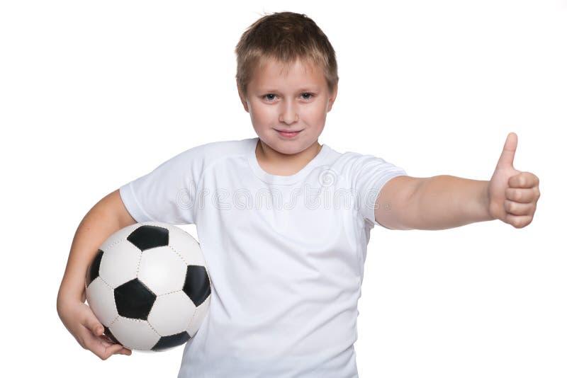 Счастливый молодой мальчик с футбольным мячом стоковая фотография