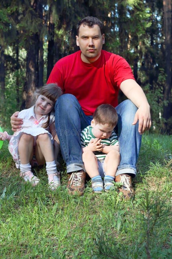 Счастливый молодой отец в красной футболке с 2 детьми стоковое изображение rf