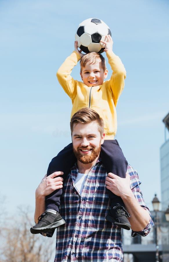 Счастливый молодой отец нося его маленького сына на плечах стоковые фотографии rf