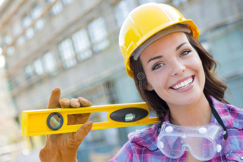 Счастливый молодой привлекательный женский рабочий-строитель нося трудную шляпу и стоковые фото